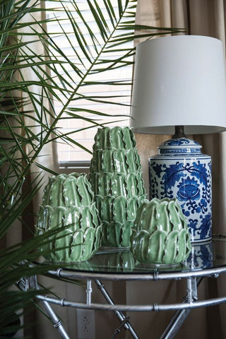 three ceramic succulent vases next to a porcelain lamp displayed on a glass side table.