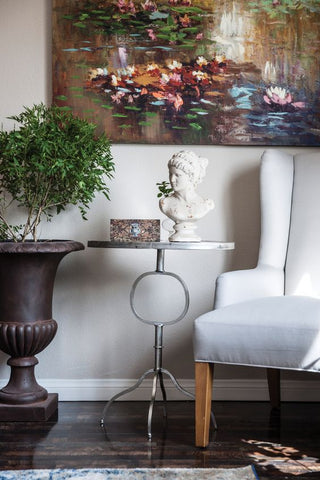 a greek vase is featured on a vintage-inspired side table alongside an indoor plant in a modern style setting.