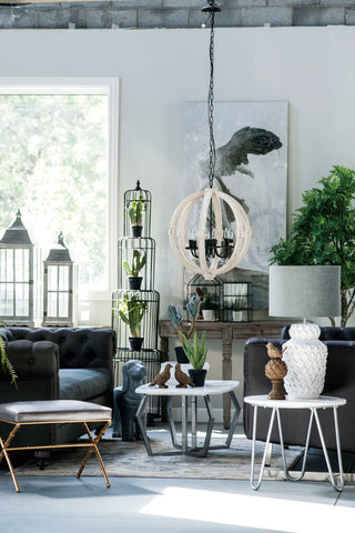 a roped-chandelier is hung in the living room amongst indoor shrubberies, vases and deco furniture.