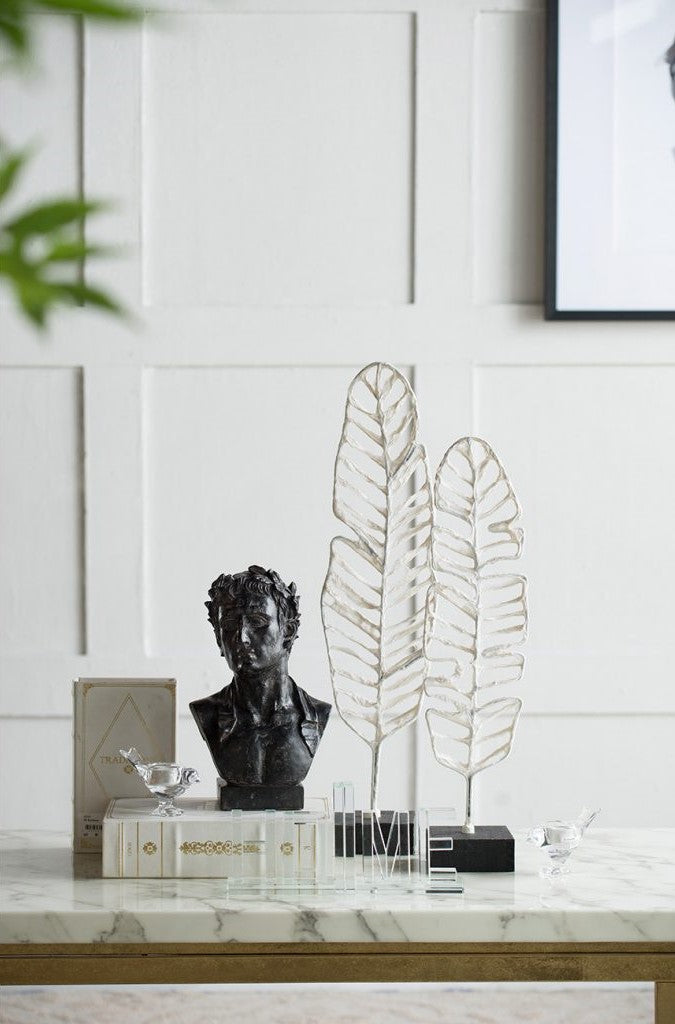 two silver feather outline sculptures are featured on a shelf alongside other trinkets