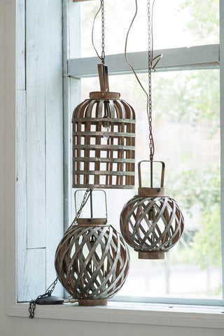 three hanging rattan lanterns by the window with natural sunlight.