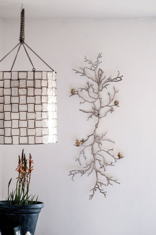 a silver branch wall art is featured next to a hanging checkered white linen lantern.