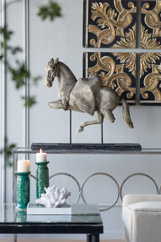 a rustic horse figurine is featured on a glass top with an embellished gold tiled wall art.