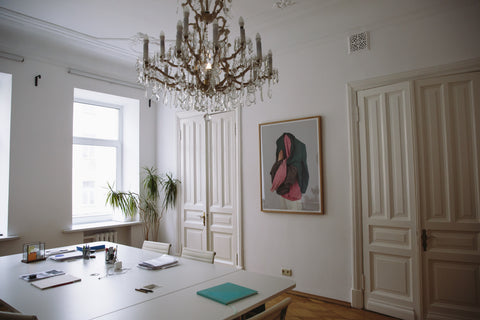 a chandelier hangs in an artistic style interior with white walls and natural sunlight.