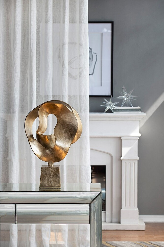 a modern gold aluminum home decor sculpture displayed in a living room