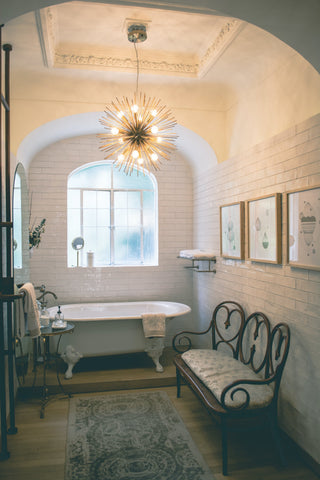 a chandelier hangs in a bathroom featuring rustic interiors with a white bathtub and metal frame furniture.