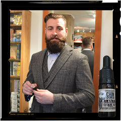 man wearing tweed suit with big beard holds a bottle of Chinsporran beard oil.