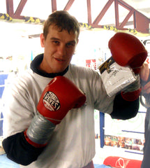 Craig McEwan pro Scottish boxer loves his cahoonas as he stands in the ring holding up a pair.