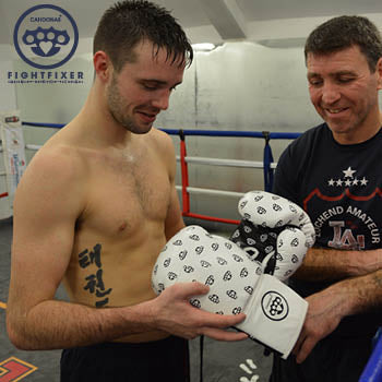Josh Taylor inspects his  new pair of FightFixer boxing gloves as Terry looks on. At Lochend Boxing club Leith