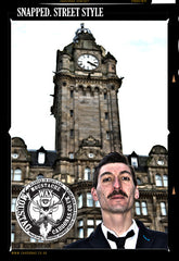 man with a large moustach stands infront of the balmoral hotel edinburgh.