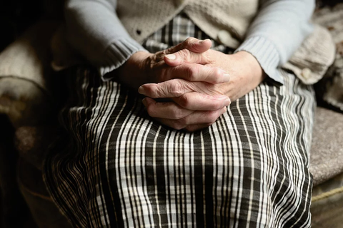 Healthspan - old woman sitting with hands clasped together