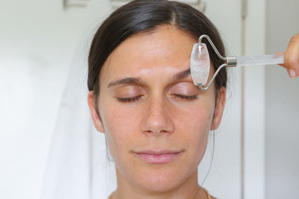adi using the clear quartz facial roller on her forehead