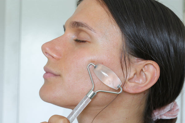 adi using the clear quartz facial roller on her cheek