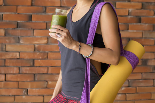 Woman drinking teami greens superfood powder before doing yoga
