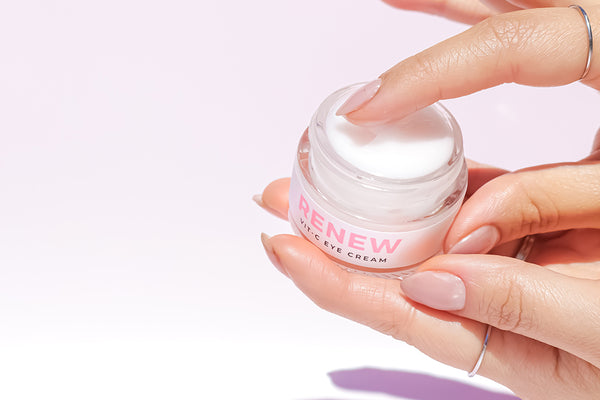 woman picking up an eye cream with her finger