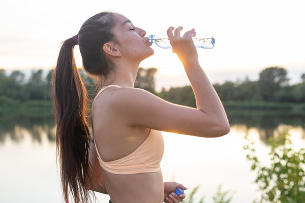 woman drinking water after going for a run