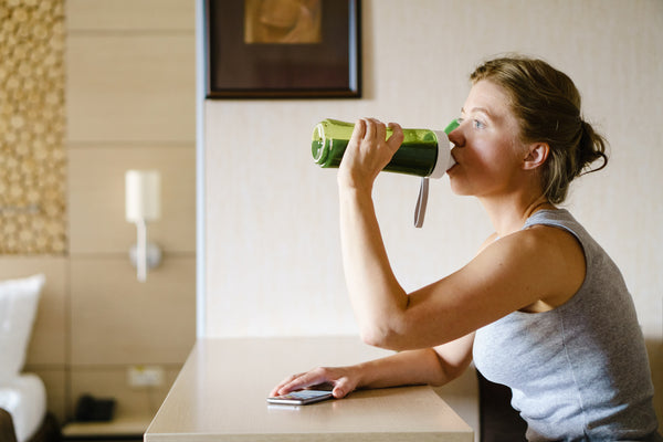woman drinking a green superfood smoothie to help her metabolism