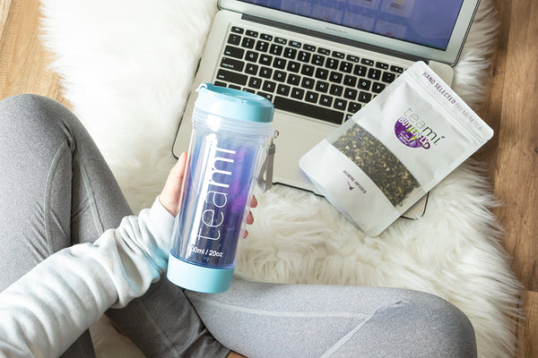 young woman working on her laptop with teami butterfly pea flower tea