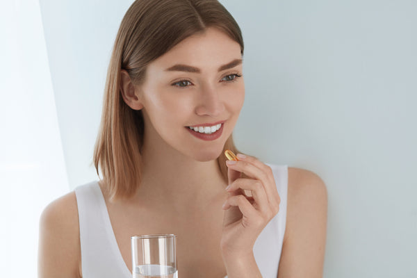 young woman taking a vitamin