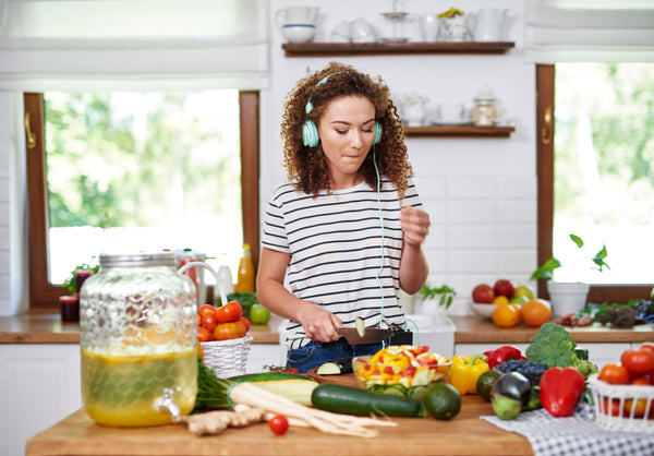 woman preparing a meal of a variety of fruits and vegetables