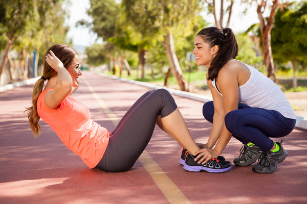 woman supporting her friend while she does sit ups