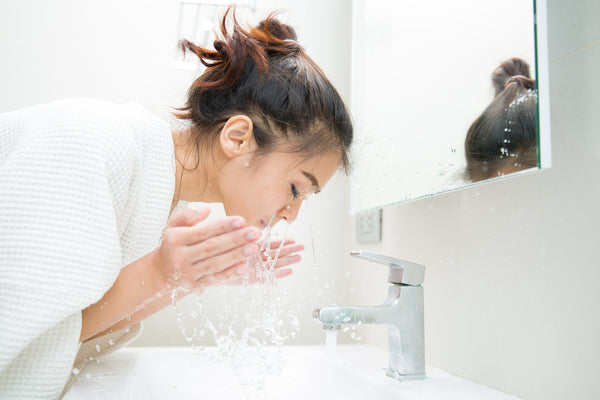 woman rinsing her face off