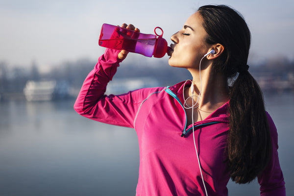 woman drinking water to stay hydrated