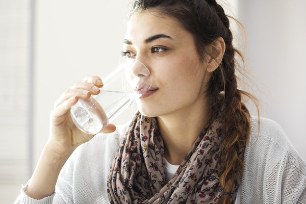 woman drinking water to cut on caffeine
