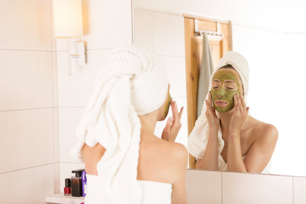 woman with green tea detox mask on her face