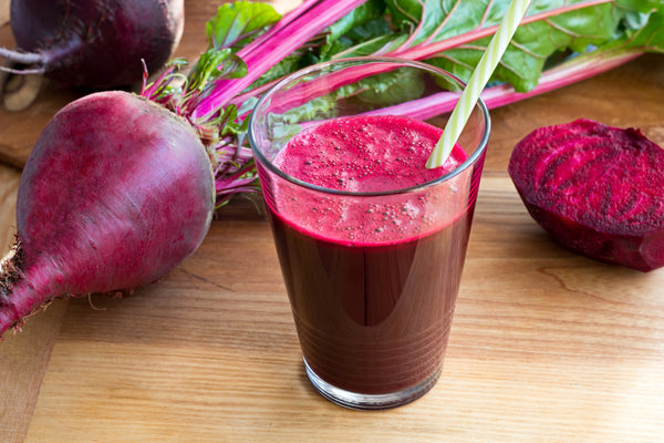 a glass of beet juice as well as some raw beet roots