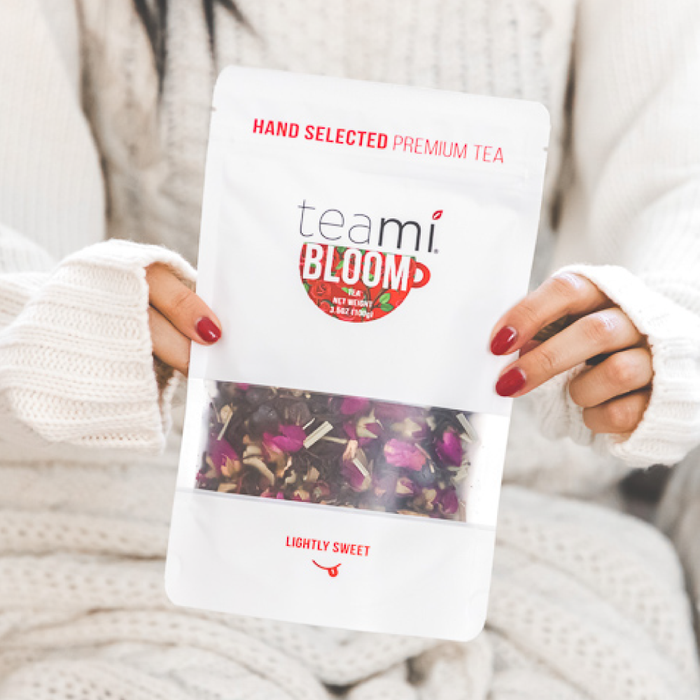 Woman holding Teami Blends Bloom Tea