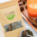 Teami Profit Tea Blend with pine cones and a candle