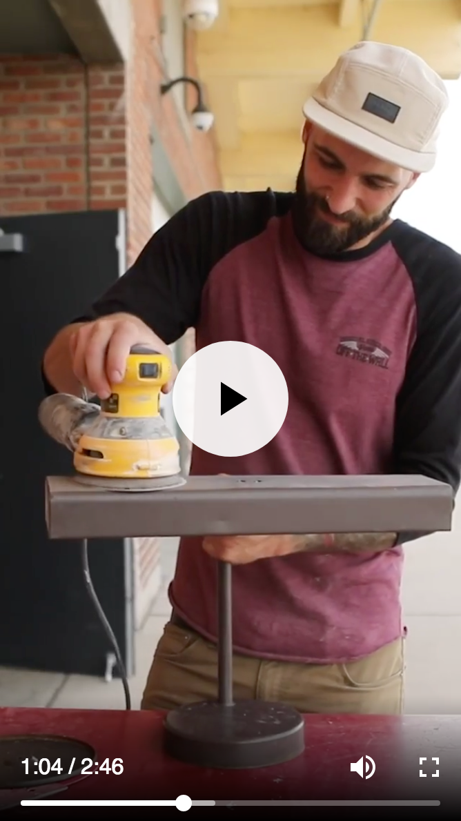 Video screenshot of man sanding top of metal desk lamp