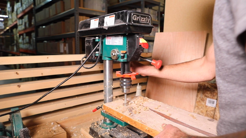 Person drilling a hole in a piece of wood with a drill press