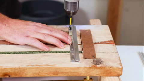 Hand drilling metal hinge onto wood board