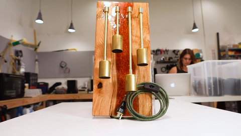 Wooden board holding bronze fixture pieces with curled electrical cord