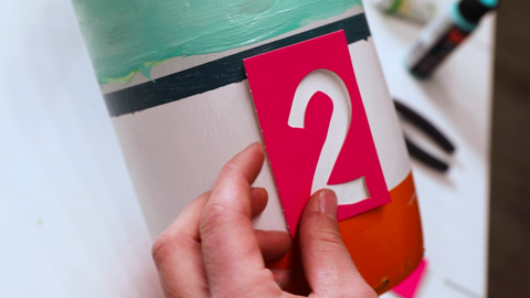 Hand holding '2' stencil over a painted object