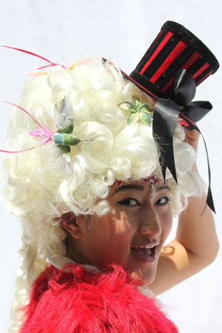 Our model is wearing the Red and Black Ringleader Mini Top Hat.