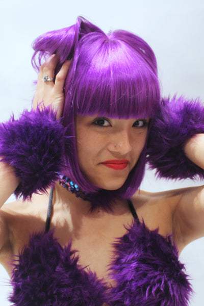 Our model is wearing the Fur Cuffs in Purple.