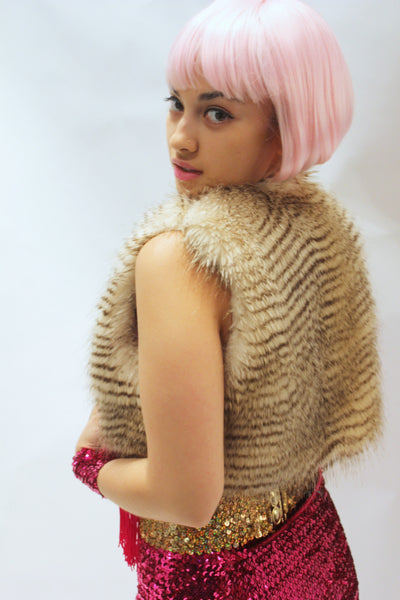 Our model is wearing the High-End Fur Bolero Vest in Blonde Raccoon.