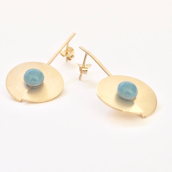 Blue long open disc earrings from the PIB collection by PLATÓNICA. Gold plated silver and glass. Minimalist jewelry. Contemporary jewelry. Author jewelry. Made in Granada, Andalusia, Spain. Jewelry workshop in the Albaicín. Crafts. Hand-made jewelry. Jewels made from Andalusia. Geometry. Modern and sophisticated style.