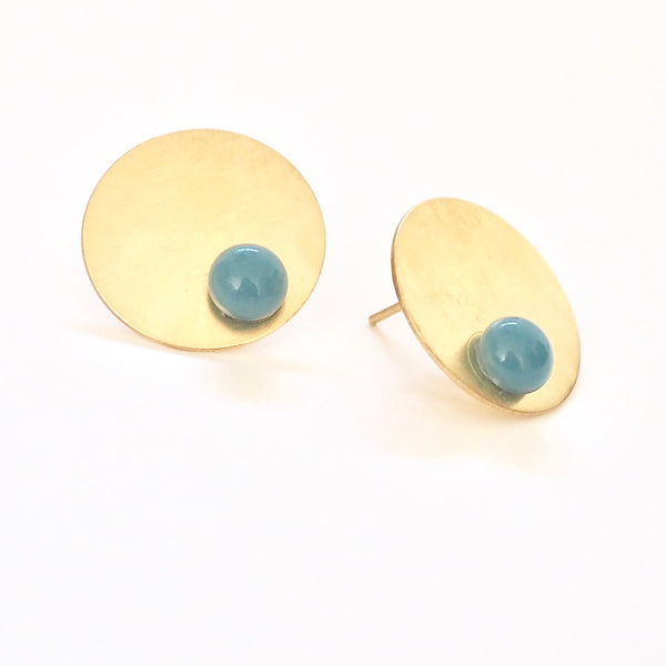 Blue disc earrings from the PIB collection by PLATÓNICA. Gold plated silver and glass. Minimalist jewelry. Contemporary jewelry. Author jewelry. Made in Granada, Andalusia, Spain. Jewelry workshop in the Albaicín. Crafts. Hand-made jewelry. Jewels made from Andalusia. Geometry. Modern and sophisticated style.