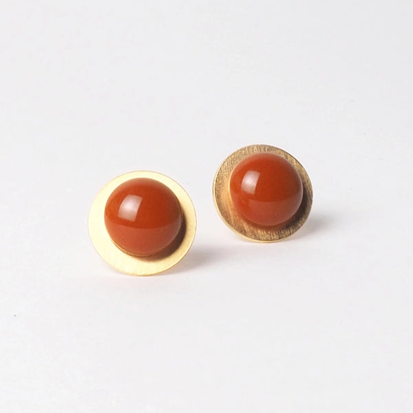 Big Orange button earrings from the PIB collection by PLATÓNICA. Gold plated silver and glass. Minimalist jewelry. Contemporary jewelry. Author jewelry. Made in Granada, Andalusia, Spain. Jewelry workshop in the Albaicín. Crafts. Hand-made jewelry. Jewels made from Andalusia. Geometry. Modern and sophisticated style.