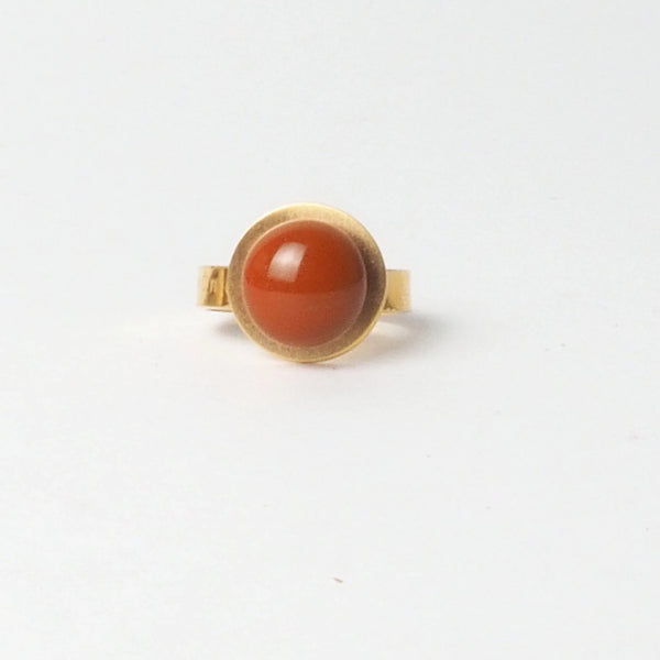 Big Orange button ring from the PIB collection by PLATÓNICA. Gold plated silver and glass. Minimalist jewelry. Contemporary jewelry. Author jewelry. Made in Granada, Andalusia, Spain. Jewelry workshop in the Albaicín. Crafts. Hand-made jewelry. Jewels made from Andalusia. Geometry. Modern and sophisticated style.