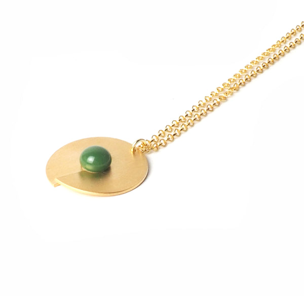 Green open disc pendant from the PIB collection by PLATÓNICA. Gold plated silver and glass. Minimalist jewelry. Contemporary jewelry. Author jewelry. Made in Granada, Andalusia, Spain. Jewelry workshop in the Albaicín. Crafts. Hand-made jewelry. Jewels made from Andalusia. Geometry. Modern and sophisticated style.