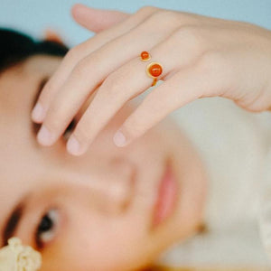 Orange double button adjustable ring from the PIB collection by PLATÓNICA. Gold plated silver and glass. Minimalist jewelry. Contemporary jewelry. Author jewelry. Made in Granada, Andalusia, Spain. Jewelry workshop in the Albaicín. Crafts. Hand-made jewelry. Jewels made from Andalusia. Geometry. Modern and sophisticated style.