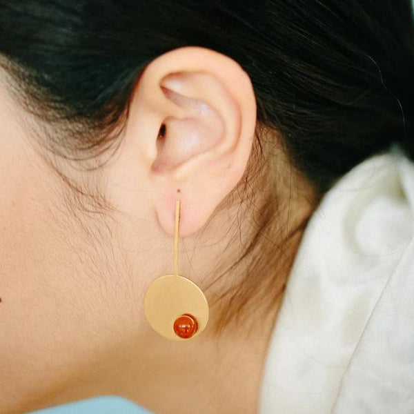 Orange long disc earrings from the PIB collection by PLATÓNICA. Gold plated silver and glass. Minimalist jewelry. Contemporary jewelry. Author jewelry. Made in Granada, Andalusia, Spain. Jewelry workshop in the Albaicín. Crafts. Hand-made jewelry. Jewels made from Andalusia. Geometry. Modern and sophisticated style.