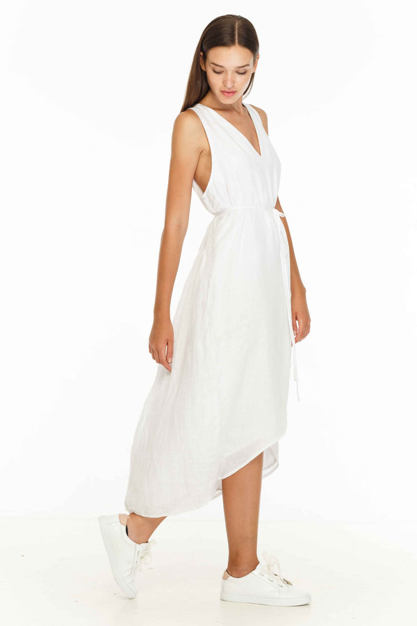 The Step Aside Dress has many features including: made of linen, v neck, tie for around the waist, back ruffle detail in a midi dress.