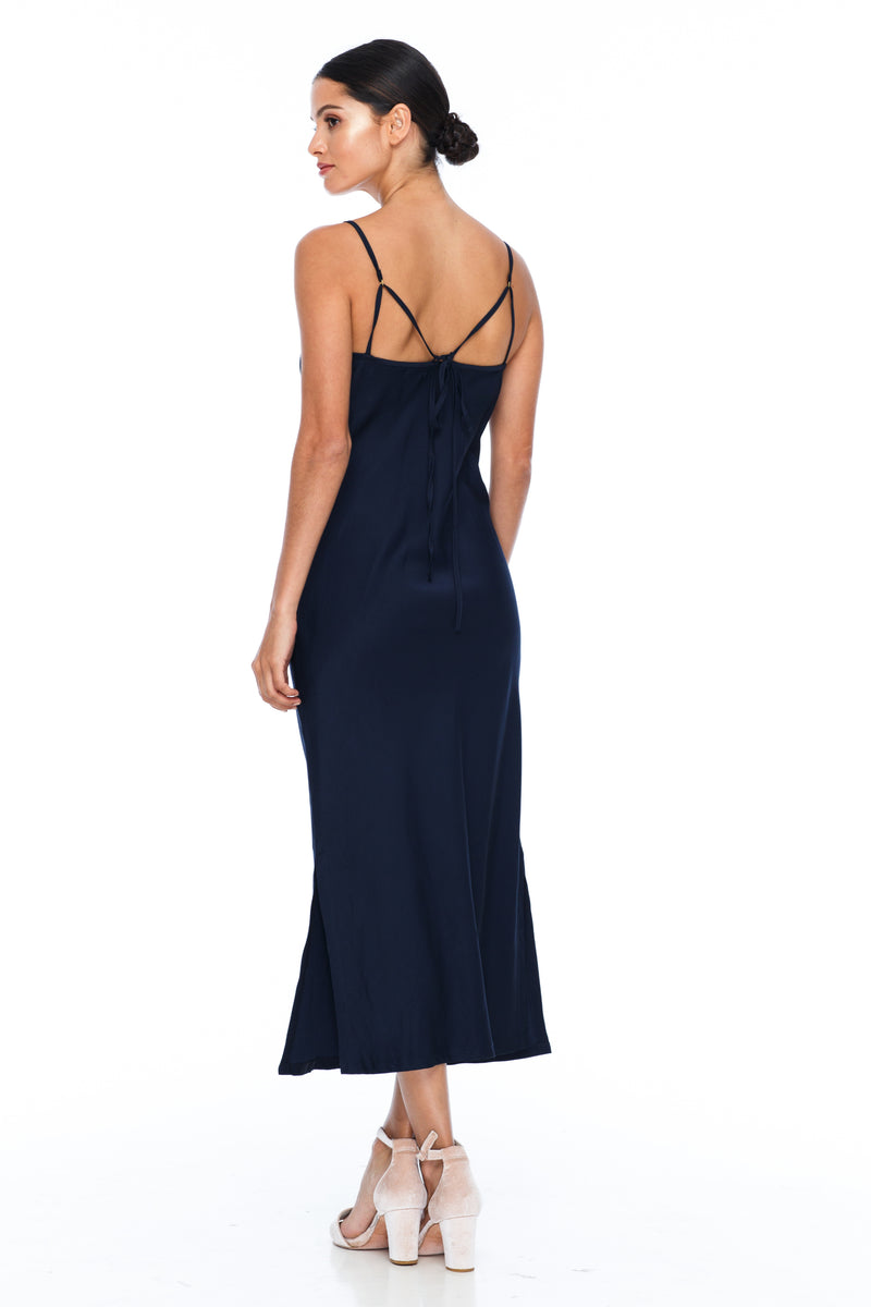 The Cairo Dress is part of the BLAK BRIDESMAIDS - Made to Order Collection.  Featuring a low v neckline and adjustable thin straps with tie detail in back. A classy chic fitted dress cut on the bias for a slinky fit.  - Midi Length  - Side Splits - Navy - Back View