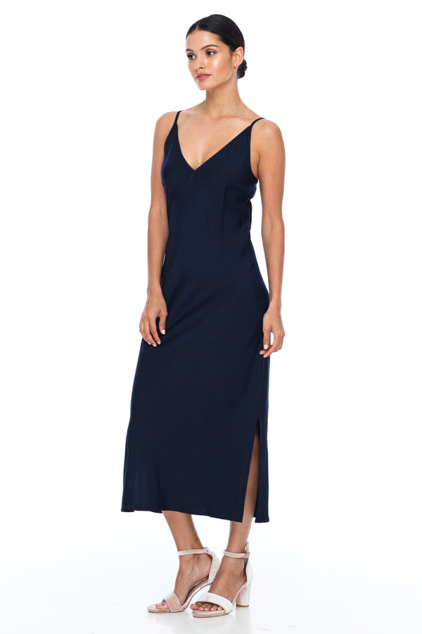 The Cairo Dress is part of the BLAK BRIDESMAIDS - Made to Order Collection.  Featuring a low v neckline and adjustable thin straps with tie detail in back. A classy chic fitted dress cut on the bias for a slinky fit.  - Midi Length  - Side Splits - Navy - Front View
